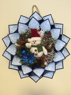 This large snowman wreath is done in shades of blue. Each cone is midnight blue in the outside. The inside is sky blue with white snowflakes. The center has holiday floral with a snowman in the center.