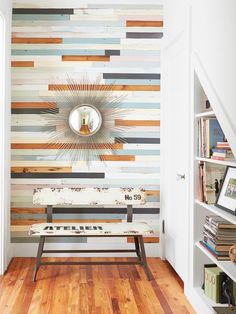 Paneled wall using leftover boards from old pine flooring nailed into place. The boards are painted shades of blue, gray, and white with a few left untouched.