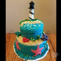 Light house, sea life birthday cake. White cake bottom tier, chocolate cake top tier, all buttercream frosting with fondant decorations and chocolate rocks. #CatsCakesAndCandles
