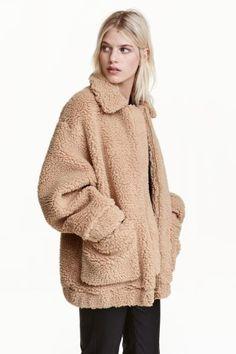 Manteau court en peluche douce. Modèle avec col, fermeture à glissière dissimulée et poches plaquées devant. Élastique à la base et en bas de manche. Doublé