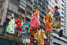 Children dressed as legendary and modern heroes are suspended above the crowd on the tips of swords and paper fans (飄色). They form the parade-in-the-air and are all secured within steel frames, though they appear to glide through the air. Parents consider it a great honour for their offspring to be part of the parade.
