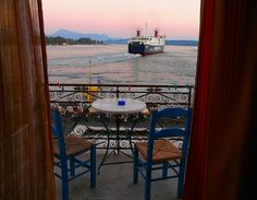Ferry boat leaving Poros island at dawn and wrought iron balcony with traditional blue wooden chairs. Poros island , Saronic Gulf, Greece