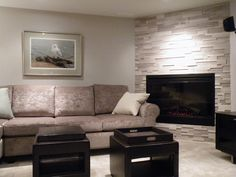 """Corner fireplace in renovated basement, featuring Erthcoverings Silver Fox stone with Dimplex 45"""" electric firebox."""