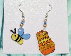 One of a kind hand painted Dangle Earrings. Pooh Bear inspired with Bee and Honey Pot To Care For: Do not wear in water or shower. Shrink Paper, Mimi Boutique, Pooh Bear, Winnie The Pooh, Dangle Earrings, Dangles, Bee, Hand Painted, Costumes