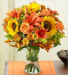 Fields of Europe for Fall from 1-800-Flowers.com.  Imagine spending a perfect autumn day browsing the bustling flower markets of Europe. It's easy with this arrangement of orange roses and lilies, vibrant sunflowers, poms and more hand-gathered in a glass gathering vase and finished off with raffia ribbon.  Get your rebate from RebateGiant.