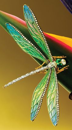 AN ART NOUVEAU ENAMEL AND DIAMOND 'DRAGONFLY' BROOCH, CIRCA 1900. Realistically designed as a dragonfly, wings set en tremblant with pliqué-a-jour enamel, edged with rose-cut diamonds, the thorax, tail and head set with old mine-cut diamonds, mounted in 18 karat yellow gold. #ArtNouveau #brooch