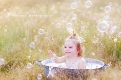 an old wash tub filled with bubble bath (and a person just out of view blowing bubbles) is such a clever idea for a capturing your little one