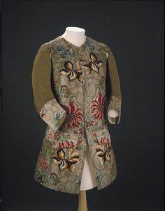 """Alla fine del Seicento - inizio del Settecento il gilet era un indumento con le maniche, portato sotto la giacca, con grossi polsini bene in vista. Durante il Settecento le maniche della giacca diventano più strette, e il gilet """"perde le maniche"""". Questo gilet di manifattura inglese (tessuto a Spitalfield, Londra), c. 1735, è in seta rigata marrone con le parti """"in vista"""" broccate in seta colorata, ciniglia e filo d'argento. Il disegno a grandi fiori è tipico delle prime decadi del…"""