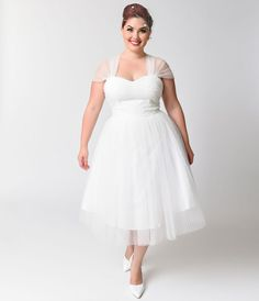 Perfect for your next garden party or afternoon tea, this plus size retro white on white swiss dotted cocktail dress will give you a feminine look thats straight out of the 1950s. The A-line shape is flattering on any womans figure, as its cinched waist