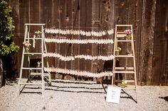 seating cards strung between to rustic ladders