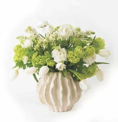 A vase of  white and green spring flowers, including viburnum tinus, white lilac, tulips and ranunculas by Judith Blacklock Flower School