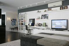 Mesa de trabalho integrada com estante de livros e TV