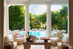 Wicker chairs from Lloyd Flanders with Michael Taylor indoor/outdoor fabric cushions surround an antique Indonesian table on the poolside terrace. Chaise lounges from country casual teak