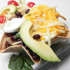 """Ecuadorian Huevos Rancheros I """"A tortilla bowl filled with black beans, onions and garlic, topped with 2 fried eggs smothered with melted cheese, avocado, and sour cream."""""""