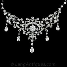 This antique bib style necklace from the 1890's is very early Edwardian. The floral and scroll motifs are fully diamond set with five pear shaped diamond set pendants. As with many pieces made at this time you can also see the influence of the Art Nouveau movement with the use of curvilinear lines. This beautiful necklace set with 4.60 carats of European and Swiss cut diamonds.
