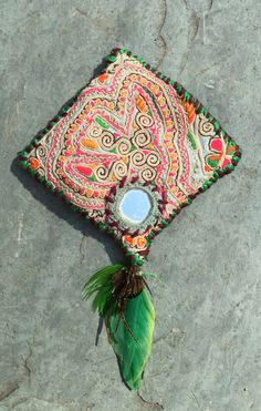 Kinship Stories: Tribal art brooch made with Hmong embroidery, Banjara mirrors and a feather. This brooch is entirely handmade and a one-of-a-kind item