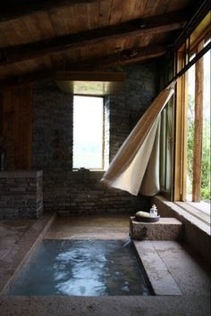 Brick   concrete. Open sunken tub. Bathroom with great wood ceiling