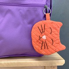 """Our friends at Art Gallery Fabrics thought it would be super fun to make """"Max"""" the cat zipper pouch with a key chain for kids to attach to their backpacks. Perfect size to add some lunch money, lip balm, and whatever other small trinkets they want to keep out and in the ready! #sewing #zip #zipper #pouch #purse #coin #lunchmoney #free #pattern #tutorial #cat #kitty #kids"""