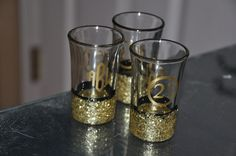 21st Birthday shot glasses. Painted black with glass paint, dipped in gold glitter then sealed with clear sealer before adding online purchased vinyl monograms/ 21 decals.