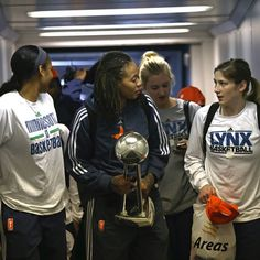 Lindsay Whalen, Seimone Augustus, Maya Moore & Rachel Jarry returning home at the airport with the WNBA Championship trophy. (Photo by David Sherman)