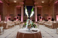 Pink uplights and the reception setup in the marbled halls of San Francisco's Asian Art Museum's Samsung Hall.