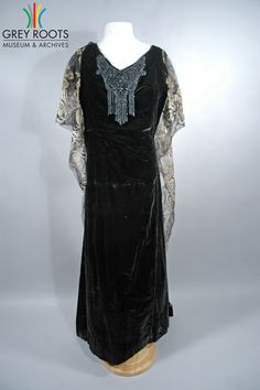A black velvet, short-sleeved, floor-length, v-necked evening dress. The dress has a train which is attached at the shoulders and is embroidered in silver and gold thread. The neck is heavily beaded and includes and dangling, beaded fringe. Grey Roots Museum & Archives Collection.