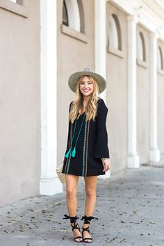 Hannah (@hannah_hagler) wears THML Clothing's black embroidered dress with a straw hat and lace-up heels for summer.