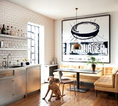 The stainless steel cabinets and dark grout in this Annabelle Selldorf–designed Manhattan apartment is softened by the custom velvet banquette underneath Andy Warhol's 1985-86 Hamburger.