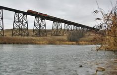 https://flic.kr/p/Bxou9s   Frozen Water Under the High Bridge - Valley City,ND   One day I may run out of angles to shoot the hi-line bridge in Valley City. Today is not that day. Westbound coalers swing across the colossal structure on a cold late November afternoon on their wayward trip across the northern plains. Obtaining this angle was a little more challenging than I had originally foreseen. The breadth of the scene was difficult to capture as I have only a 24-85 which yields…