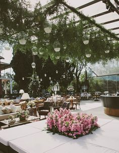 Hanging Glass Lantern and lush green foliage to decorate the ceiling creates a very soft, romantic and inviting reception area. Beautiful neutral color table tops. With accents of pink flowers create a very inviting space to celebrate during the reception.