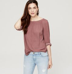 Dotted with tiny orchids, this flowy woven style is beautifully shirred for can't-resist pretty. Ballet neck. Long sleeves with button cuffs. Keyhole back with double button and loop closure. Shirttail hem.