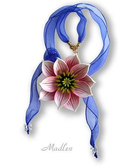polymer clay. Like the sheer ribbon and ends haning below the pendant but metalic beads and nicer flower. Like the concept.