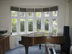 Roman blinds all round bay window in Andrew Martin silk