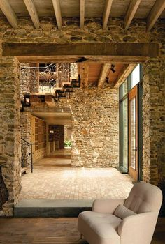 A two-story skylit entry hall announces the public entrance. A two-story skylit entry hall announces the public entrance. Slicing through the house from front to back, the atrium ho. Open Staircase, Brick And Stone, Stone Walls, Brick Walls, Entry Hall, Entry Doors, Stone Houses, Stone Cottages, Country Cottages