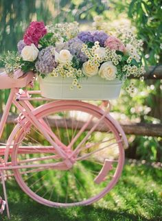powder pink bike with a bicycle basket full of fresh picked bouquet of flowers that include roses - hydrangeas - lavender -sweet feminine girly treats . love the green outdoor garden