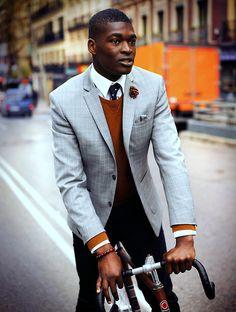 glen plaid jacket, orange sweater, white shirt, black patterned tie, black jeans