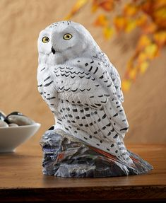Perched on a dark, lichen-covered rock, a snowy owl takes a break from hunting lemmings and ptarmigan on the treeless northern tundra. A striking tabletop sculpture, beautifully replicating the origin