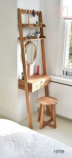 An ultimate space saver with an oak working surface a vertical sliding circular make-up face mirror 7 hanging metal pegs 2 shelves and 2 drawers with handles.
