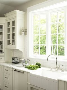 all white kitchen with herringbone subway tile, polished nickel sconces, bow window, glass front cabinets, apron sink.