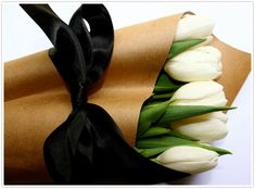 Tie a black bow around a bunch of white tulips wrapped in butcher paper for an easy and chic hostess gift #ribbon