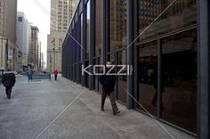 view of a man walking. - Image of a man walking by office building.