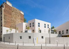 A crumpled white shell patterned with tiny perforations wraps around this cluster of small-scale buildings that form a children's centre in Paris.
