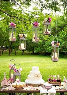 The centerpiece of the garden party is this cake table with hanging lanterns of candles and flowers