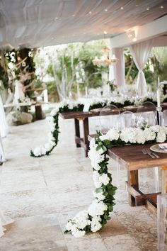 Wedding guest table decor in Kukua Punta Cana, Dominican Republic  Table runners made of fresh flowers  Photo by Karina Jensen Photography