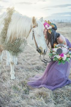 Flower child horse, pretty white horse getting kissed by lady in long purple dress with flowers in her hair.
