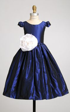 SHOWN: Royal Blue Silk taffeta    White silk Peony & crinoline sold separately   Ballet neckline, natural waist, full ball gown skirt, sleeves (choice of length).  100% silk, fully lined. Made in USA.  Hand rolled silk Peony flower (shown in white) sold separately.     Sizes Silk Taffeta   0-3 $225   4-8 240   10-16 270   in Knee or Tea length    for ANKLE +15