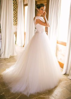 The beautiful bride is wearing a stunning Monique Lhuillier tulle wedding ball gown.