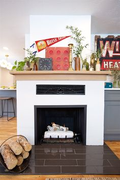 Boise Boys | Timber And Love | Luke Caldwell | HGTV | Realty | Mid Century | home renovation | Design | Boise Idaho | white fire place | wooden mantel | plants | living room | mantel decor ideas