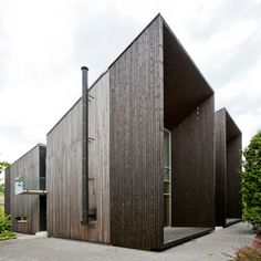 These twin residences in Riga, Latvia, mirror one another exactly, except that one is clad in timber and the other in blackened steel.
