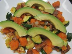 Sausage, sweet potato, onion and zuchini stir fry breakfast, topped with organic avocado. Yummy